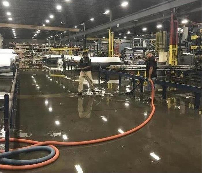 Warehouse filled with machinery. The ceiling lights are reflecting off the flooded floor like a light show
