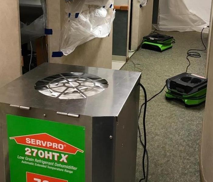 Dentist office hallway.  Servpro drying equipment is in place and there are barriers set up