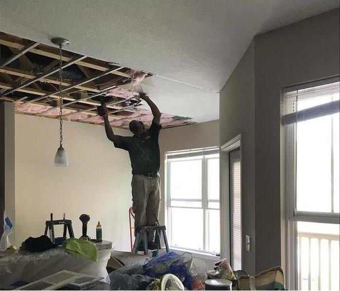 Servpro technician is on a ladder replacing ceiling panels that have water damage from upper apartment fire.